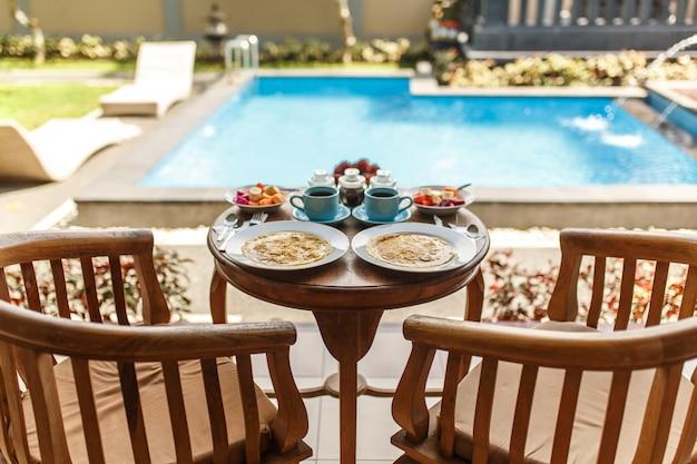 木製のテーブルに2つの青いカップの温かい飲み物と伝統的なバリの朝食。