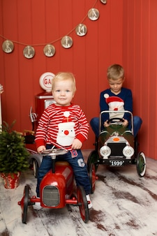 かわいい2人の弟がおもちゃの車で遊んでいます。幸せな子供時代。