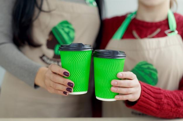 エプロンの2人のバリスタが緑の持ち帰り用の紙コップでホットコーヒーを保持しています。