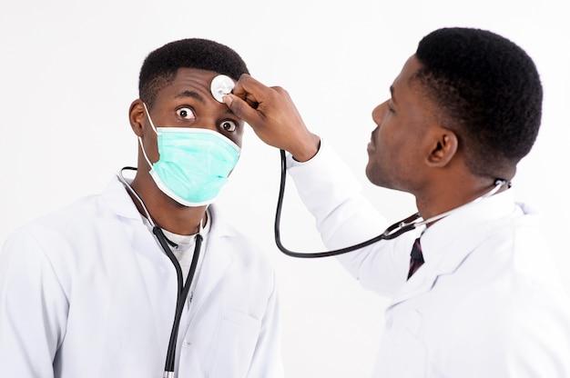 2 молодых африканских доктора на изолированной белизне с фонендоскопом. один из них с маской.