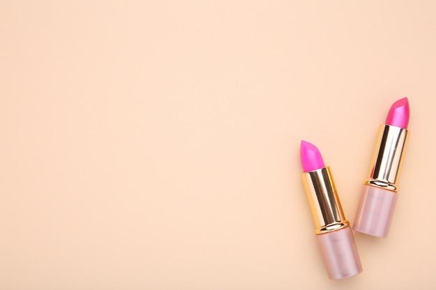 ベージュのテーブルに2つのピンクの口紅