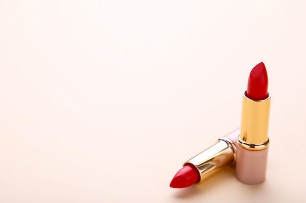 ベージュ色の背景に2つの赤い口紅をクローズアップ