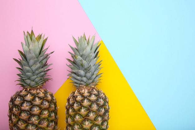 カラフルな背景に2つの熟したパイナップル