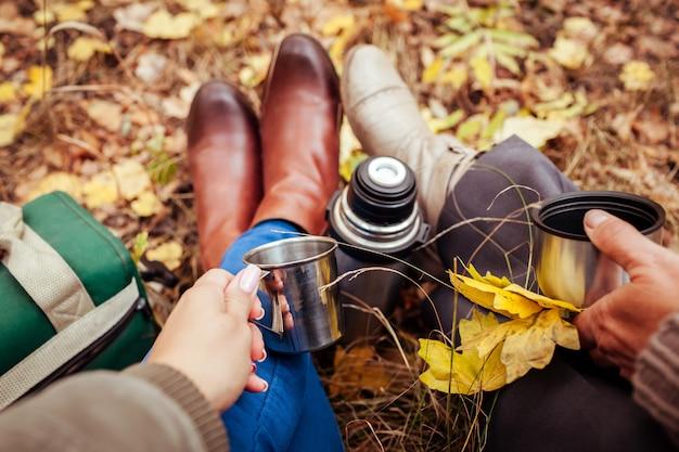 秋の森でお茶を飲んでいる2人の旅行者