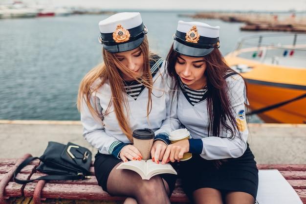制服を着て海で本を読んで海洋アカデミーの2人の女子大生。勉強している友達