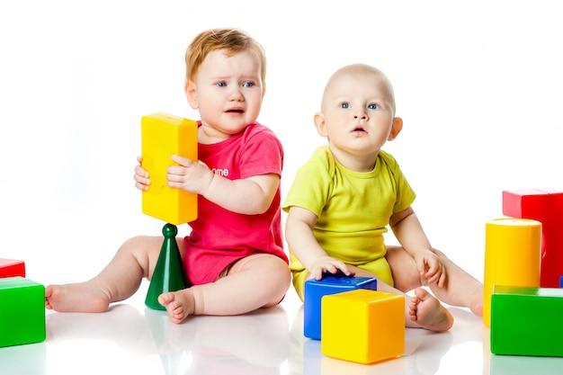 2人の子供は明るい服でサイコロ、ピラミッド、タンブラーをします