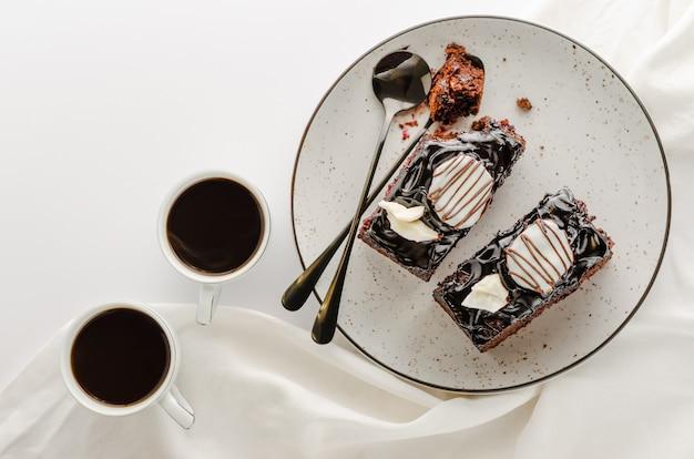 艶をかけられたチョコレートケーキと白い背景の上のコーヒーの2つのスライス