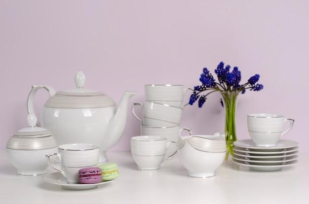 2つのマカロンと磁器や食器の紅茶とコーヒーは白いテーブルの上の青い花で設定。