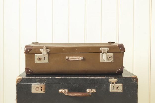 2つの古いレトロなスーツケースホワイトウッドヴィンテージティントコピースペース