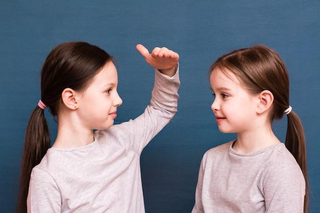 2人の女の子の姉妹は青い背景に手のひらでお互いの成長を比較します