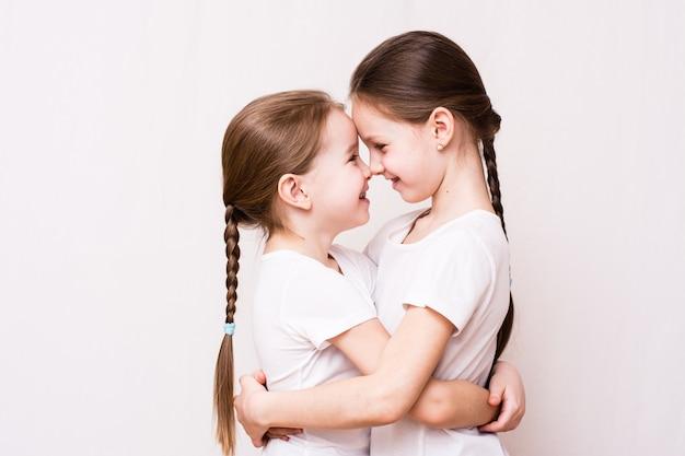 2人の女の子の姉妹は、会うときに優しくお互いを抱きしめます