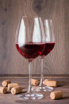 赤ワインとコルクの木製テーブルの上の2つのメガネ