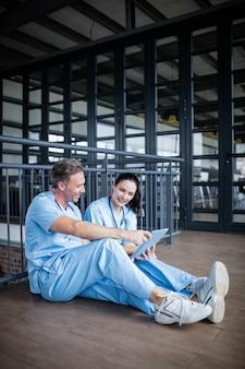 床に座って、病院で話している2人の看護師