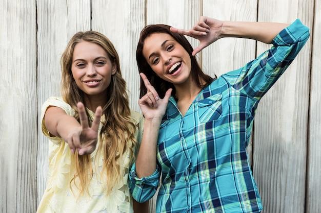 平和のジェスチャーを作る2つの笑顔の若い女性