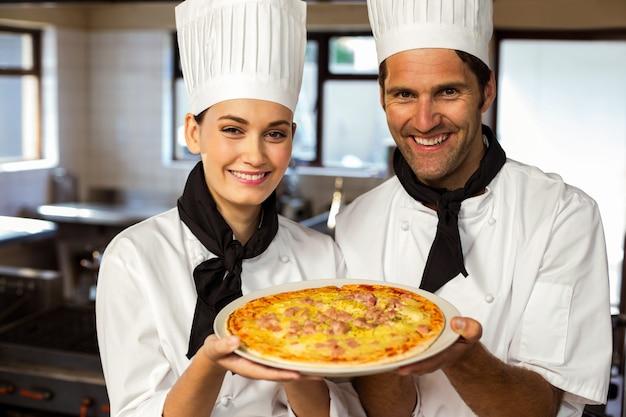 ピザを提示する2人のシェフの肖像画