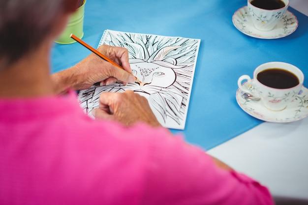 2杯のコーヒーと紙のシートに描くライオン