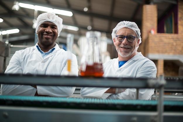 腕を組んで立っている2人の工場エンジニアの肖像画
