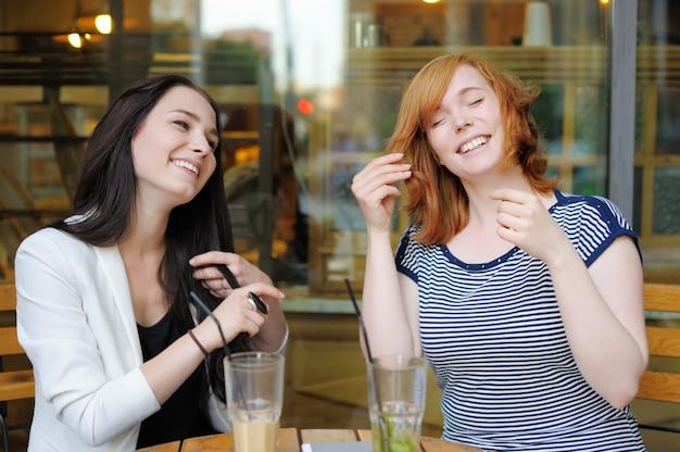 屋外カフェで楽しんで2人の若い女性