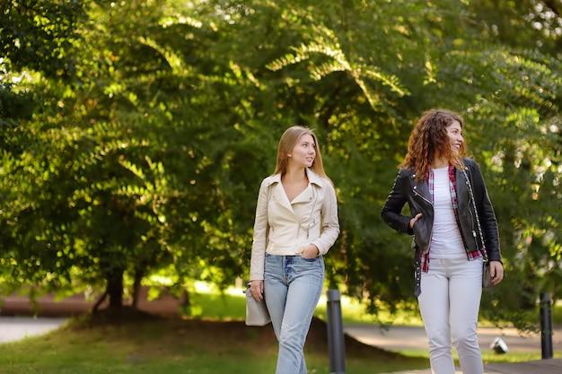 日当たりの良い公園を歩きながら話している2人の美しい若い女性。コミュニケーションとゴシップ