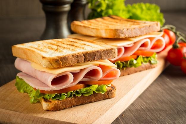ベーコン、サラミ、生ハム、新鮮な野菜と素朴な木製のまな板の上の2つのサンドイッチのクローズアップ。クラブサンドイッチのコンセプト。
