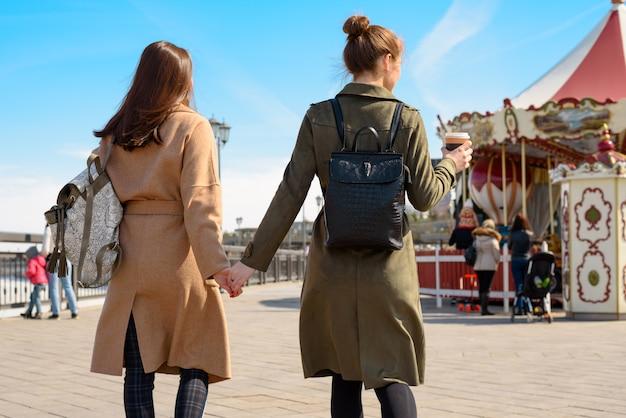 背中を持つ2人の女性の肖像画、コートとバックパックで通りを歩き、手をつないで