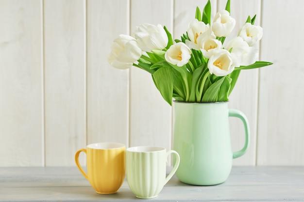 花瓶と2つのマグカップで新鮮な白いチューリップの花束