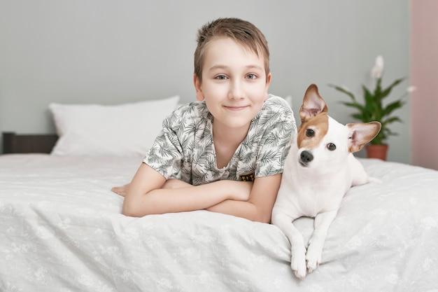 2人の友人の少年と犬が一緒にベッドに横たわっています。犬ジャックラッセルテリアとベッドの上の少年。友情の概念。