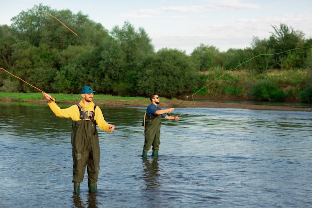 ゴム長靴を着て川に2人の漁師が立っています。