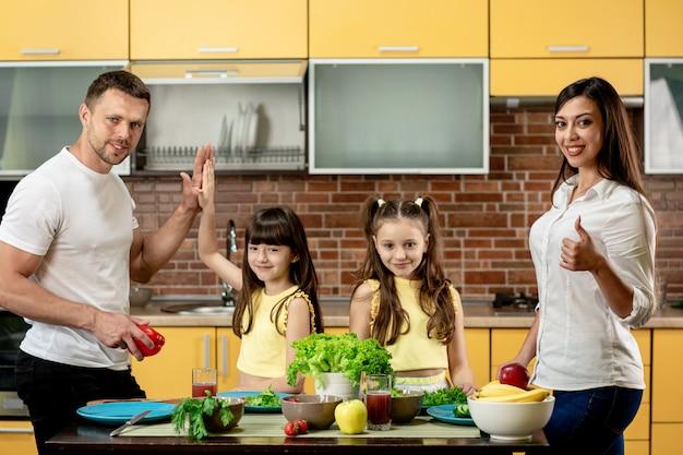Милая маленькая девочка 2 и ее красивые родители варя овощи в кухне дома. счастливая семья, мама папа и две дочери, глядя в камеру