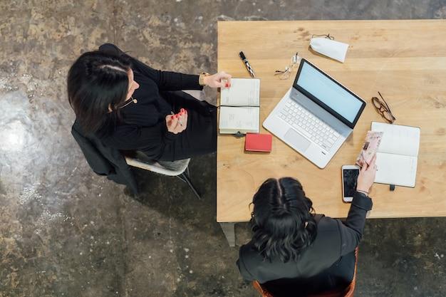 オーバーヘッドビュー2人の若い女性屋内座っている作業机