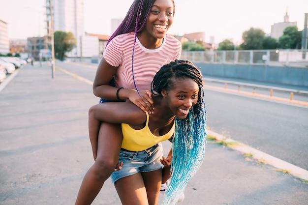 おんぶに乗ってハグを楽しんで屋外2人の姉妹黒人女性