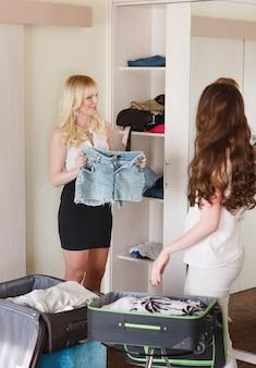 2人の女性の友人がホテルの部屋でスーツケースを収集します。
