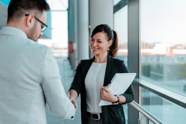2つの笑みを浮かべてビジネス人々握手。良い取引。