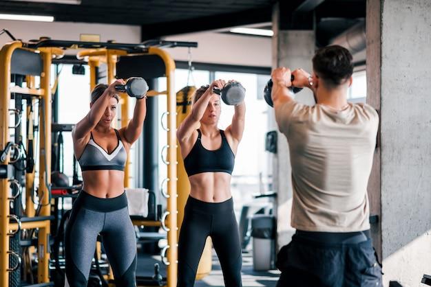 2人の筋肉女性がジムでトレーナーとワークアウト。