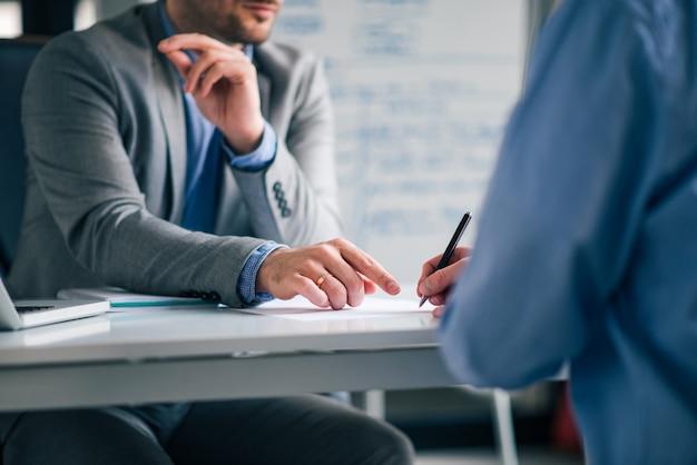 Изображение низкого угла 2 людей в официально носке сидя на столе и и подписывая соглашение.
