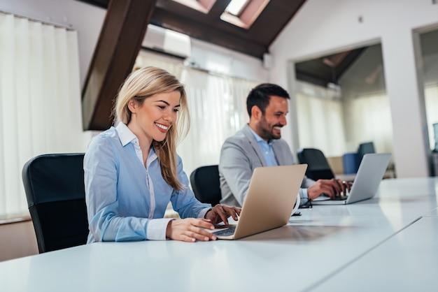 オープンオフィスのスペースでラップトップに取り組んでいる2人のビジネス人々。