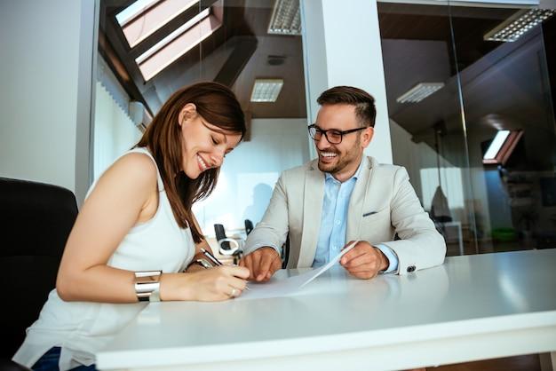 一緒に座っている2人の起業家が書類を比較して事務机で働いて