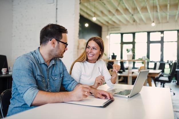 2人の同僚が近代的なオフィスに作業中に議論します。