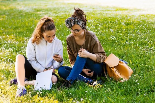 公園の芝生の上に座っている2人の女性