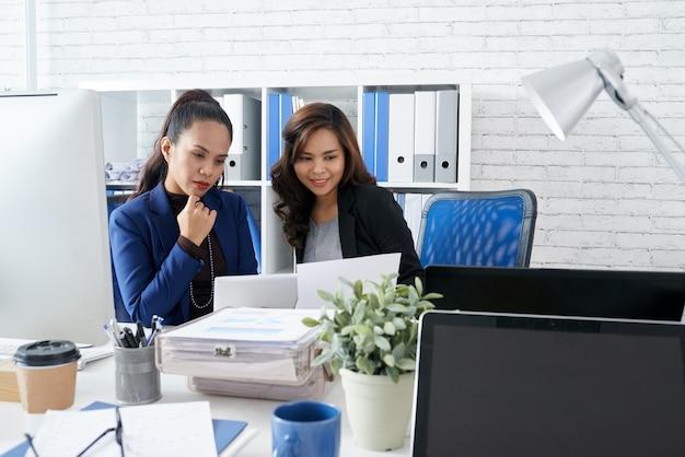 2 азиатских женских коллеги сидя совместно в офисе и смотря документ