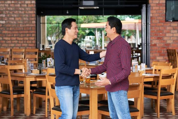 カフェでお互いに挨拶する2人の仲間の側面図