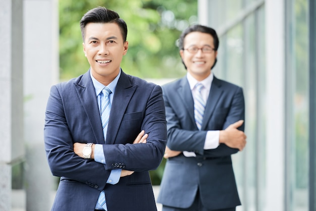 腕を組んで屋外に立っている2人のアジアのビジネスマンのウエストショット