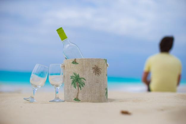白ワインとエキゾチックな砂浜で2つのグラスのボトル