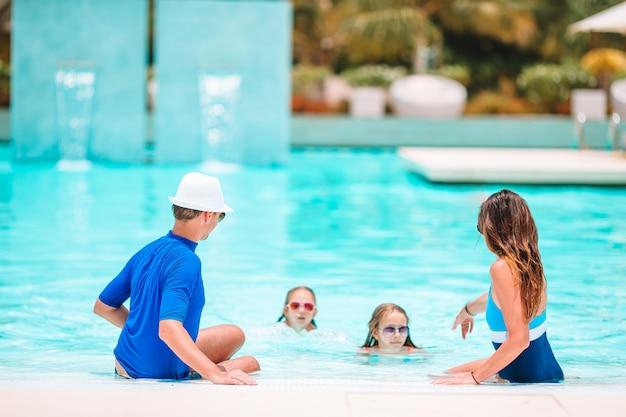 2人の子供を持つ若い家族は屋外プールで夏休みを楽しむ