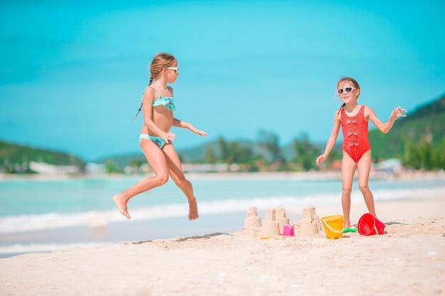砂の城を作ると熱帯のビーチで楽しんでいる2人の子供