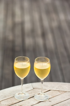 木製のテーブルに夕暮れ時のおいしい白ワインを2杯