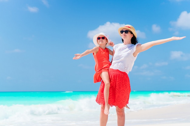 熱帯のビーチでのかわいい女の子と若い母親。 2人家族は夏休み中にたくさん楽しい