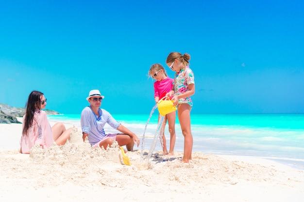 熱帯のビーチで砂の城を作る2人の子供連れのご家族