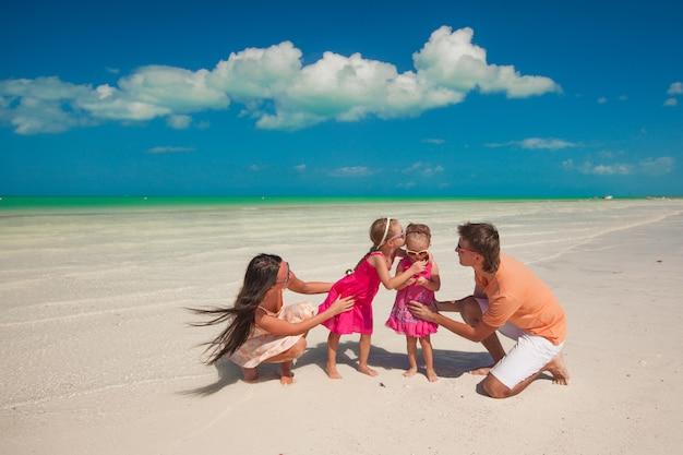 2人の娘がビーチで楽しんで若い美しい家族
