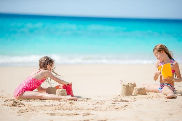 砂の城を作り、熱帯のビーチで楽しんで2人の子供